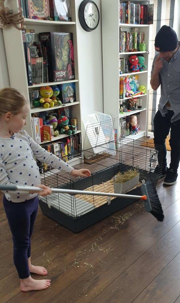 Young girl sweeping wooden floor cleaning animal cage with man