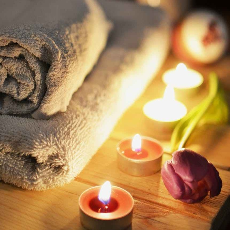 Towels in spa setting with candles and flower