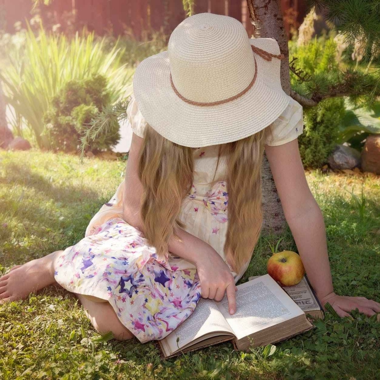 Girl reading book in garden with apple