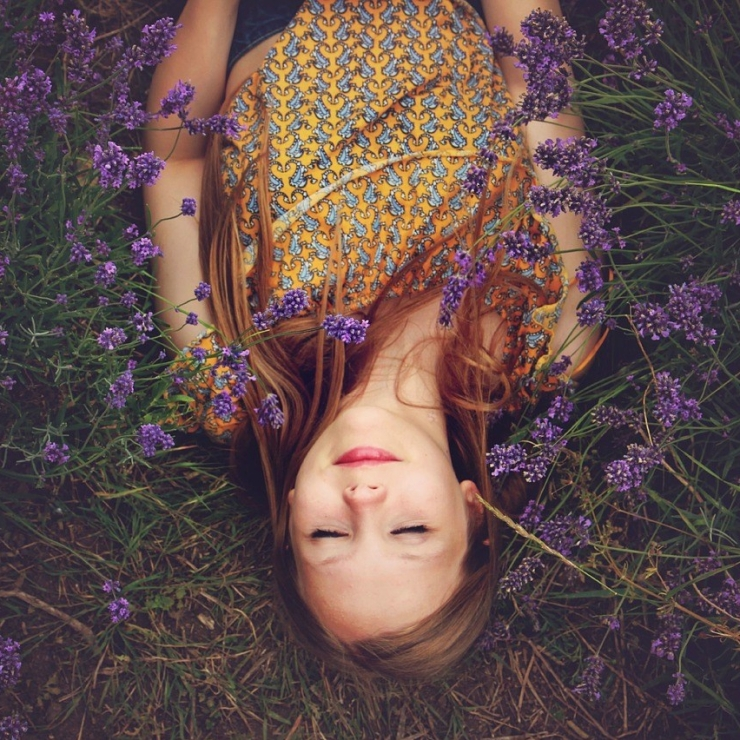 Girl lay down on grass with lavender