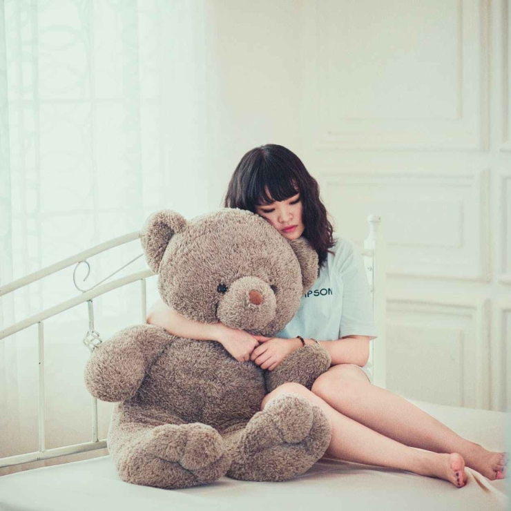 Sad adult female hugging giant teddy on bed
