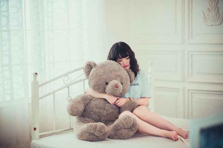 Sad adult female hugging giant teddy on bed